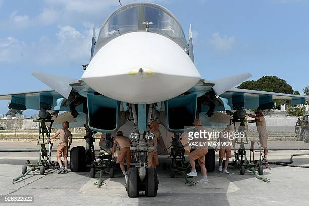 Russian servicemen prepare an SU34 fighter jet for a mission from the Russian Hmeimim military base in Latakia province in the northwest of Syria on...