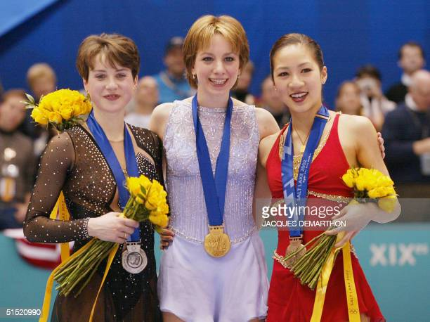 Russian silver medalist Irina Slutskaya US gold medalist Sarah Hughes and US Michelle Kwan smile on the podium after the women's figure skating event...