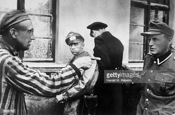 A Russian slave labourer amongst prisoners liberated by the US Armoured Division of the 1st US army points at a former Nazi guard who brutally beat...
