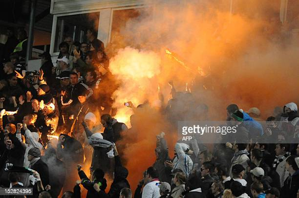 Russian soccer fans light flares during a fourth round Russia Cup match between Dinamo Moscow and Torpedo Moscow at the Eduard Streltsov Stadium in...