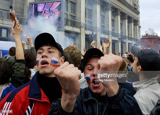 Russian soccer fans shout in front of the Kremlin as they watch the Russian soccer team lose to Japan in a televised 2002 World Cup match in Moscow...