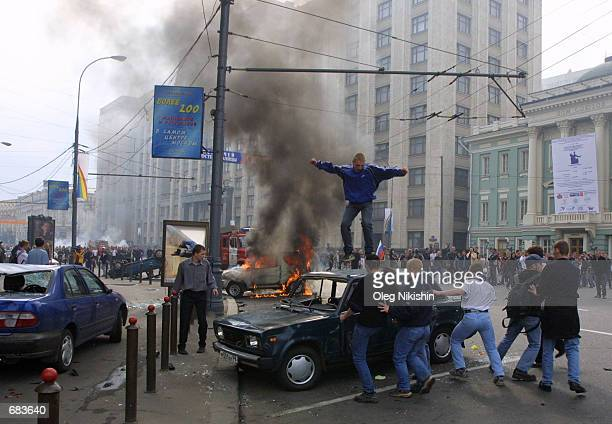 Russian soccer fans smash up a car in front of the State Duma, Russia's lower house of parliament located less than a half a mile from the Kremlin on...
