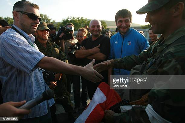 A Russian soldier accepts the gift of a Gerogian flag in a gesture of peace whilst a convoy of Russian armour heads along the main road from Gori...
