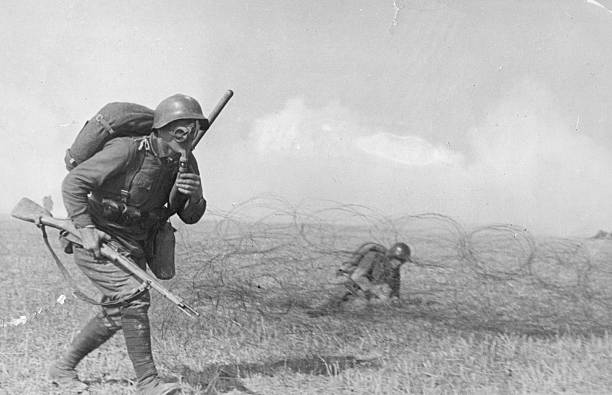 A Russian soldier advances, equipped with full breathing...