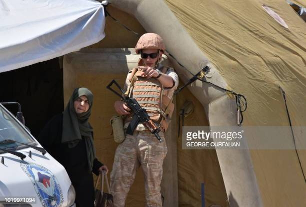 A Russian soldier directs a Syrian woman at the Abu Duhur crossing on the eastern edge of Idlib province on August 20 2018 Civilians are coming from...
