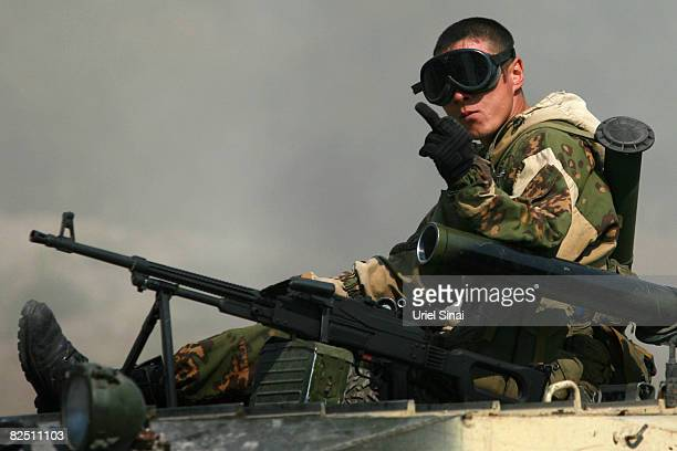 A Russian soldier gestures as he rides an APC August 22 2008 near Igoeti on the road from Tbilisi to Gori Georgia According to reports Russian troops...