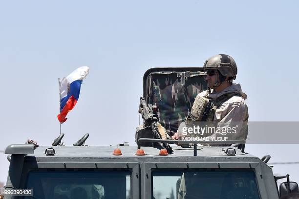 Russian soldier guards a checkpoint as displaced Syrians from the Daraa province come back to their hometown in Bosra, southwestern Syria, on July...