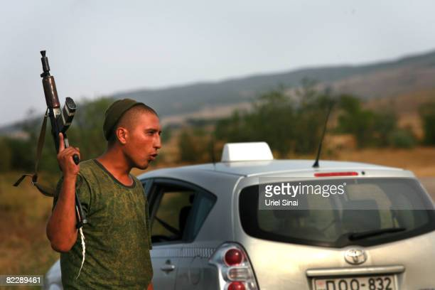 A Russian soldier holds his weapon as a Russian military convoy pass the town of Gori August 13 Georgia Russia has denied reports of Russian troops...