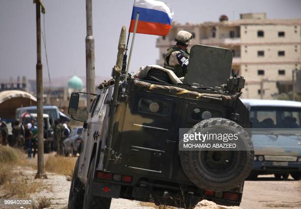 Russian soldier on his armoured vehicle watches Syrian rebels during evacuation from Daraa city, on July 15 as Syrian government forces heavily...