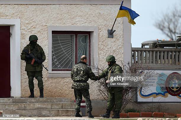 Russian soldier shakes hands with a Ukrainian military man outside a Ukrainian military base on March 19 2014 in Perevalnoe Ukraine Russia's...