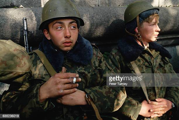 A Russian soldier smokes a cigarette while another waits nearby during the violent conflict at the Russian White House on October 4 1993 Led by...