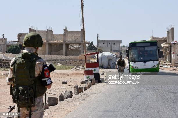A Russian soldier stands guard at the Abu Duhur crossing on the eastern edge of Idlib province on September 25 as Syrians cross from rebelheld areas...