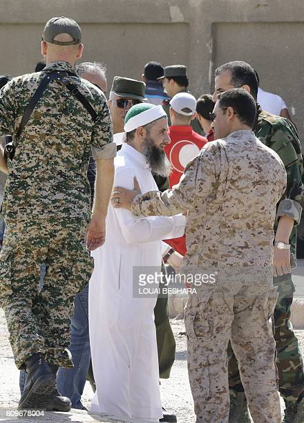 A Russian soldier stands next to Syrian army officers shaking hands with a cleric from the Waer neighbourhood in the central city of Homs during the...