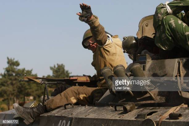 A Russian soldier waves while a convoy of Russian armour heads along the main road from Gori towards Tblisi as the tense standoff on the north of...