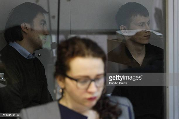 Russian soldiers Capt Yevgeny Yerofeyev and Sgt Alexander Alexandrov captured while fighting in wartorn eastern Ukraine sit behind a glass window...
