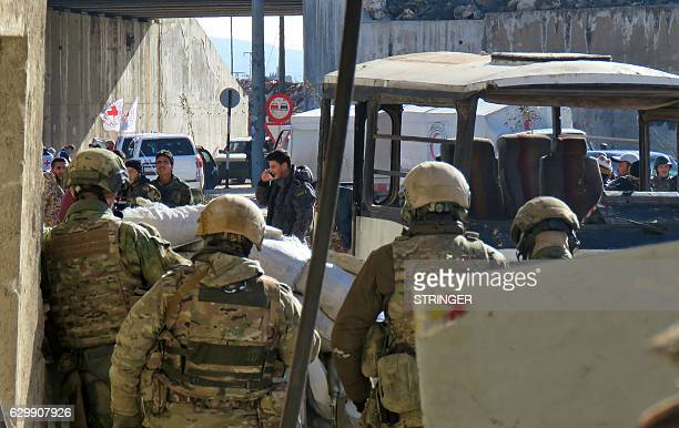 Russian soldiers gather in the government held side of the embattled city of Aleppo before the start on an evacuation operation of rebel fighters and...