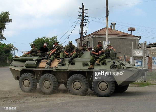 Russian soldiers leave the port of Poti Georgia which they briefly occupied on August 19 2008 At the back of the vehicle are two men wearing white...