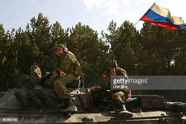 Russian soldiers look on while a convoy of Russian armour heads along the main road from Gori towards Tblisi as the tense standoff on the north of...