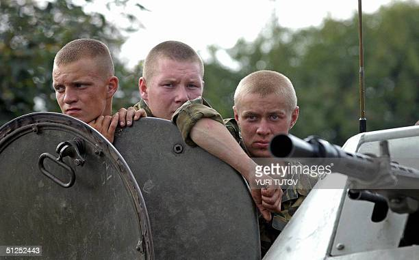Russian soldiers on a top of the APC wait on their position near the school where a group of gunmen wearing belts laden with explosives are holding...