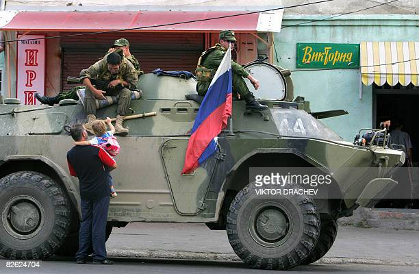 Russian soldiers on an APC greet a South Ossetian child and a man in Tskhinvali on September 2 2008 Russian Prime Minister Vladimir Putin praised...