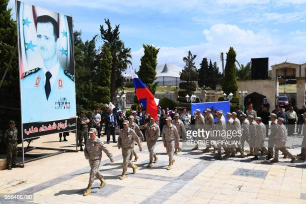 Russian soldiers parade in front of a poster of Syrian president Bashar alAsad during a ceremony marking Soviet victory over Nazi Germany in WW II in...