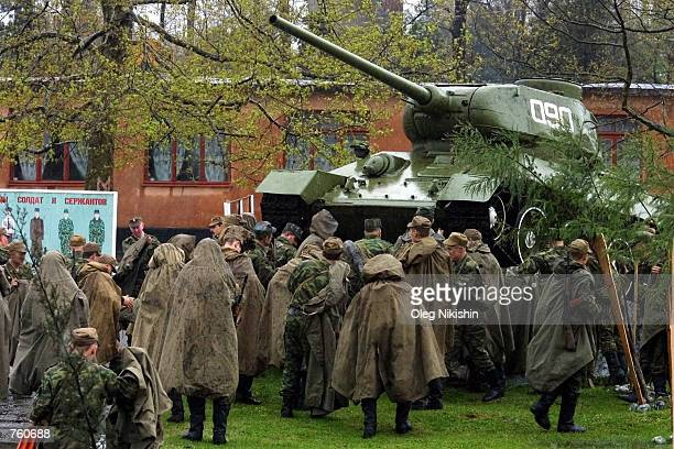 Russian soldiers stand in the rain near a tank dating back from WWII at the Russian military base April 8 2002 in Batumi Georgia Relations have been...