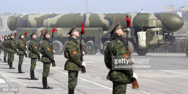 Russian soldiers stand near a TopolM ICBM while participating in a rehearsal for the nation's Victory Day parade outside Moscow in Alabino on April...
