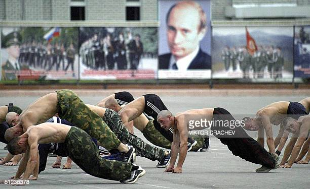 Russian soldiers train in front of a portrait of Russian President Vladimir Putin at the military unit in Khankala, 30 August 2004. With all the...