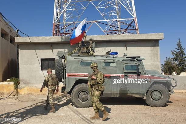 Russian soldiers walk past a Russian military police armoured vehicle at a position in the northeastern Syrian city Kobane also known as Ain alArab...