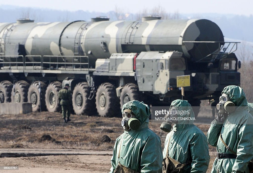 Russian soldiers wear chemical protection suits as they stand next to a military fueler on the base of a prime mover of Russian Topol intercontinental ballistic missile during a training session at the Serpukhov's military missile forces research institute some 100km outside Moscow on April 6, 2010. The US-Russia nuclear arms treaty to be signed this week enhances trust between the Cold War foes but Moscow may quit the pact if US missile defence plans go too far, a top Russian official said Tuesday.