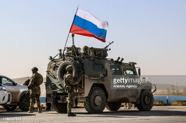 Russian soldiers, with Russian flag, are seen on armoured vehicle as they enter the base at the Tishrin Dam on the Euphrates, which the US troops'...