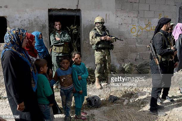 A Russian solider looks on near Syrian fighters and villagers as a Russian military convoy arrives in Kaoukab a small village near the city of Hama...