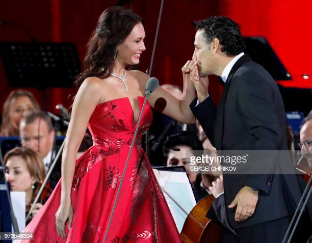 Russian soprano Aida Garifullina and Peruvian tenor Juan Diego Florez react on stage after performing during a galaconcert dedicated to the Russia...