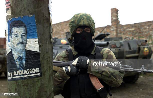 A Russian special forces officer stands next to a poster of Chechen President Alu Alkhanov on a street of Grozny 05 November 2004 Russian forces...
