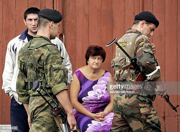 Russian special forces soldiers pass by relatives of hostages outside the school, where a group of gunmen, wearing belts laden with explosives, are...