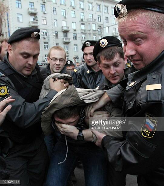 Russian special police officers catch an opposition supporter during the Day of Anger protest rally against Mayor Yury Luzhkov in central Moscow on...