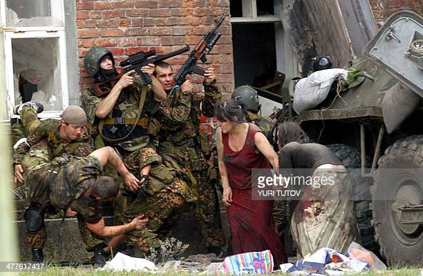 A Russian special police soldier carries an injured colleague as two soldiers and two women take cover behind the APC during the rescue operation of...