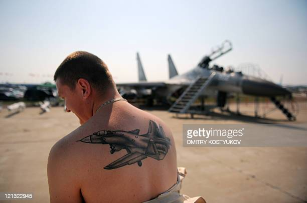 Russian specialist shows his tattoo in front of a Su-30 during MAKS-2011, the International Aviation and Space Show, in Zhukovsky, outside Moscow, on...