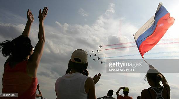 Russian spectators wave as the French aerobatic team Patrouille de France performs over Zhukovsky airfield, outside Moscow, 25 August 2007, during...