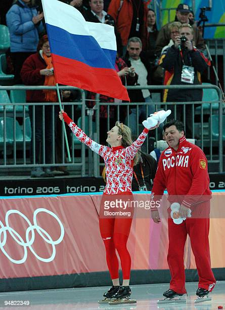 Russian speed skater Svetlana Zhurova left waves to the crowd with a Russian flag and a stuffed animal a fan has given her after winning the gold...
