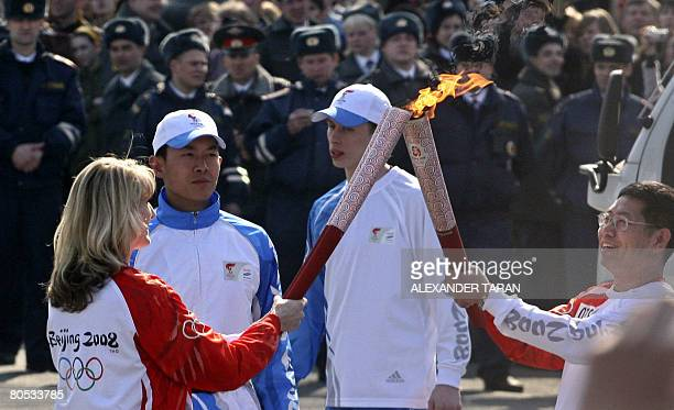 Russian speedskating Olympic champion Svetlana Zhurova receives the Olympic flame from Chinese Consul General in StPetersburg Tien Erhlung during a...