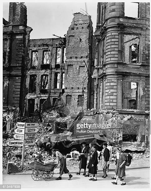 A Russian street sign among the ruins in the Nollendorf Platz Berliners pass a damaged German tank buried in the rubble of the street | Location...