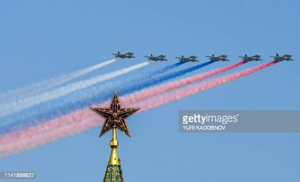 TOPSHOT Russian SU25 assault aircrafts release smoke in the colours of the Russian flag while flying over Moscow's Kremlin Borovitskaya tower during...