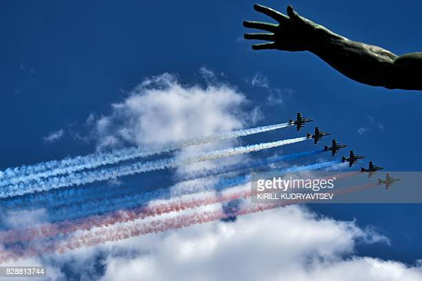TOPSHOT Russian Su25 assault aircrafts release smoke in the colours of the Russian flag while flying over Red Square during the Victory Day military...