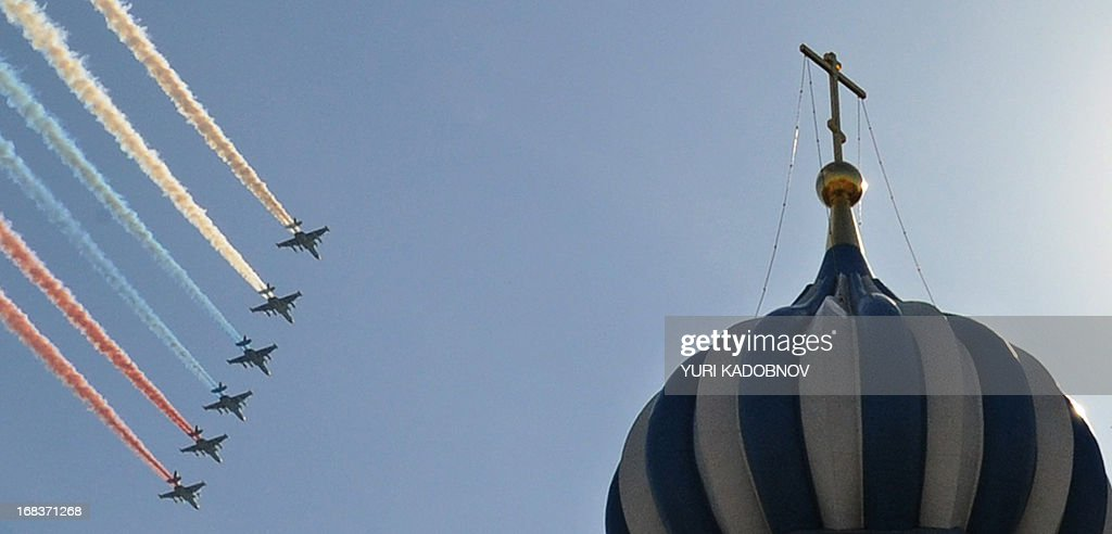KADOBNOV -- Russian Su-25 attack aircraft release smoke in the colours of the Russian flag while flying over the Red Square in Moscow, on May 9, 2013, during Victory Day parade. Fighter jets screamed over Red Square and heavy tanks rumbled over its cobblestones as Russia flexed today its military muscle on the anniversary of its costly victory over Nazi Germany in World War II.
