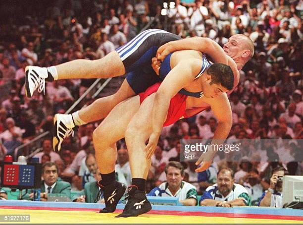 Russian super heavyweight wrestler Alexander Karelin topples opponent Omrane Ayari of Tunisia on his way to winning their 130kg Olympic preliminary...