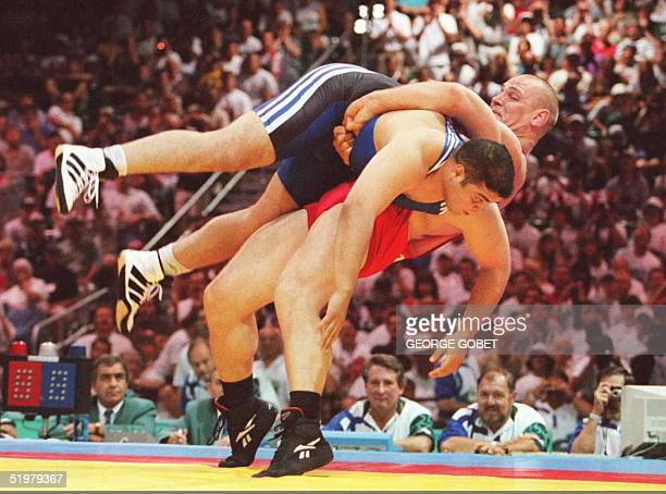 Russian super heavyweight wrestler Alexander Karelin topples opponent Omrane Ayari of Tunisia on his way to winning their 130 kg Olympic preliminary...