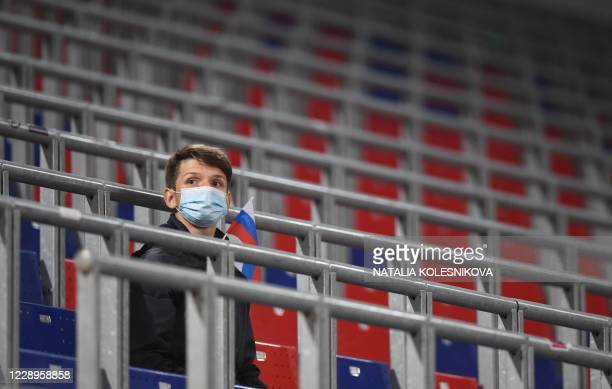 Russian supporter wearing a face mask as a preventive measure against the Covid-19 disease caused by the novel coronavirus sits on a stadium tribune...