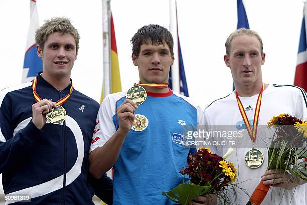 Russian swimmer and winner Vladimir Dyatchin third placed German Thomas Lurz and second placed Briton David Davies pose after the men's 10 km event...
