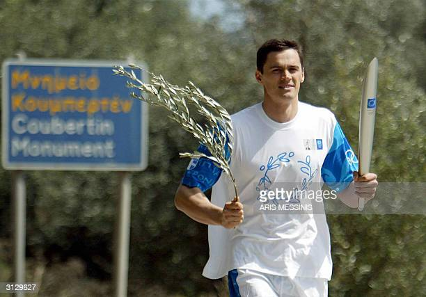 Russian Swimming Olympic Champion Alexander Popov runs with the Olympic flame in Ancient Olympia March 25 2004 More than 11000 torchbearers will...